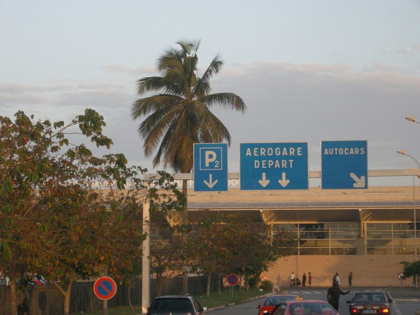"Photograph of palm tree signs reading ""P2 / Aerogare Deaprt / Autocars"" outside an airport terminal"